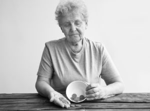 Financial industry fraud elderly woman holding bowl with a couple of coins in hand looking down sad