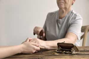 Money coins falling out onto table from open wallet purse as young woman holds hand of elderly woman sitting in chair with walking cane in other hand