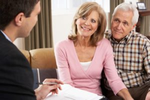 Senior citizens couple meeting with daily money manager smiling financial management