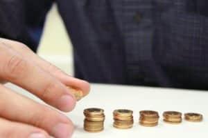 Senior money management elderly person hand organizing gold coins money into stacks