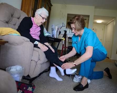 In home nurse senior citizen aid helping elder woman put on her shoes
