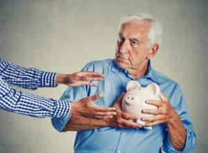 elderly man holding piggy bank to avoid elder abuse cases