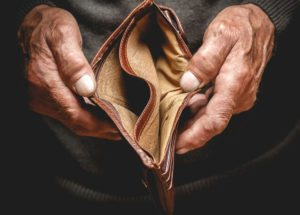 Victim of elderly abuse holding open empty wallet