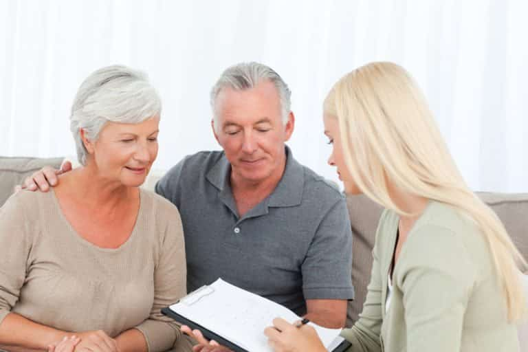 Elderly couple sitting with a money manager
