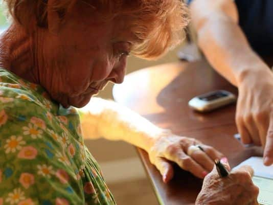 Elder woman writing a check falling victim of elderly financial abuse and fraud